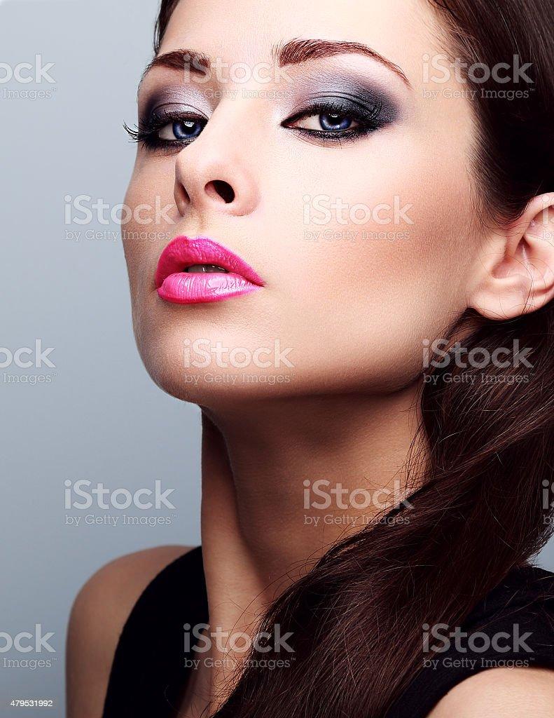 Beautiful woman with bright smokey makeup eyes and pink lipstick stock photo