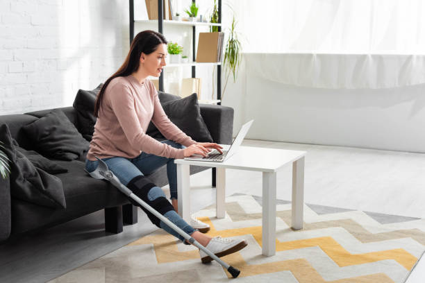beautiful woman with broken leg having online consultation with doctor on laptop at home stock photo