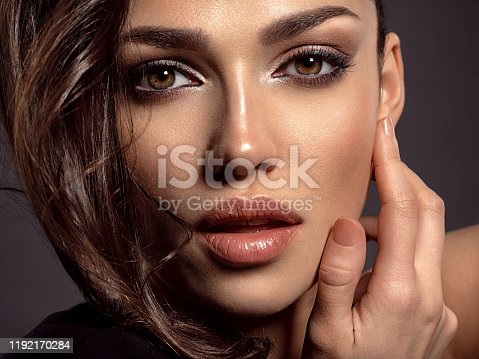 Beautiful woman with brown hair. Attractive model with brown eyes. Fashion model with a smokey makeup. Closeup portrait of a pretty woman looks at camera.