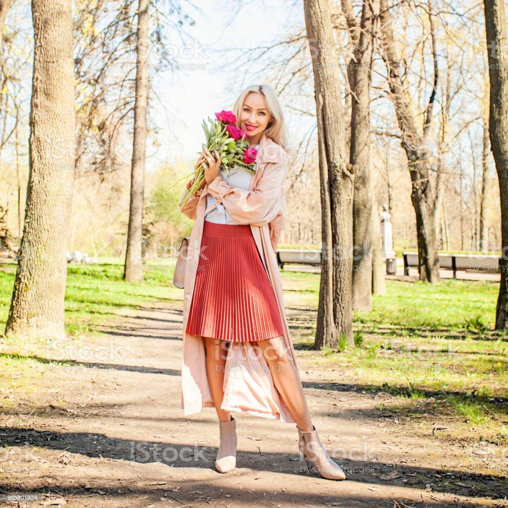 Belle femme avec bouquet de fleurs à l'extérieur. Modèle féminin pivoine dans le parc - Photo