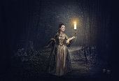 Beautiful woman with candle in medieval dress on foggy road