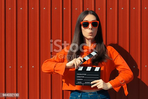 istock Beautiful Woman with Cinema Clapper on Red Background 944032130
