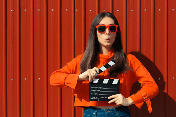 beautiful woman with cinema clapper on red background - audition stock photos and pictures