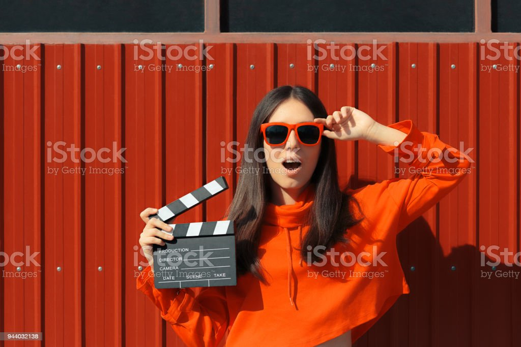 Beautiful Woman with Cinema Clapper on Red Background stock photo