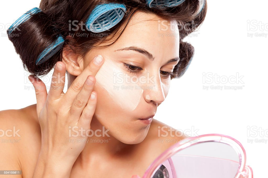 Beautiful woman with curlers applying poorly chosen foundation stock photo
