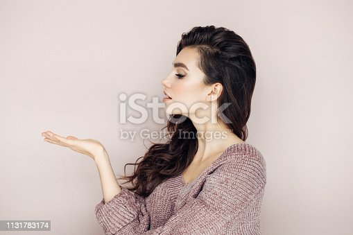 928358464istockphoto Beautiful woman with curly hair demonstrates your product 1131783174