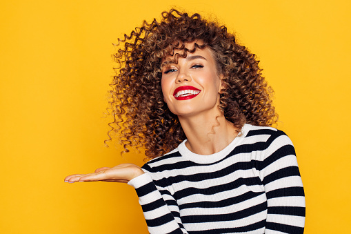 928358464 istock photo Beautiful woman with curly hair demonstrates your product 1254652483