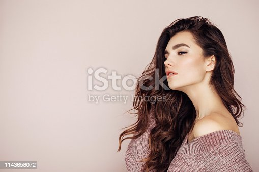 928358464istockphoto Beautiful woman with curly hair 1143658072