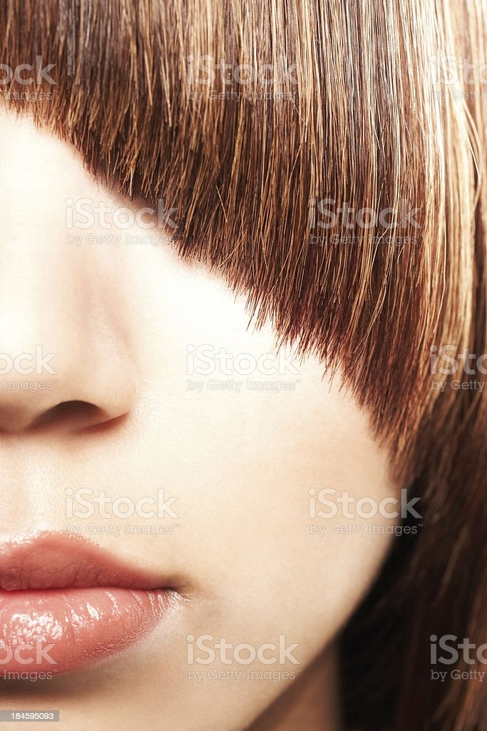 Beautiful woman with eyes obscured by dramatic curved bangs royalty-free stock photo