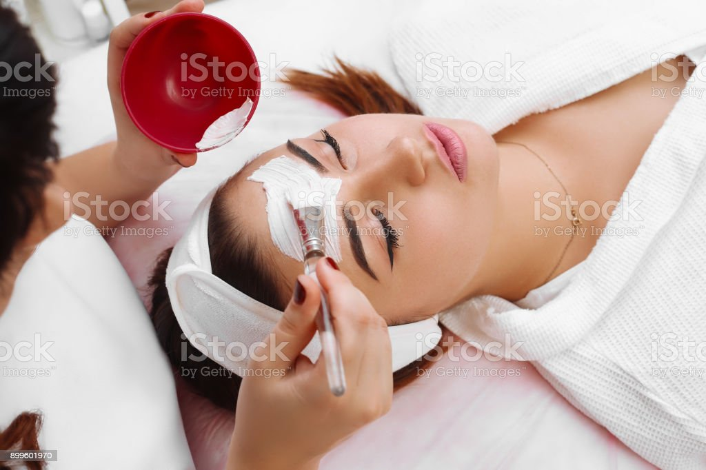 Beautiful woman with facial mask at beauty salon stock photo