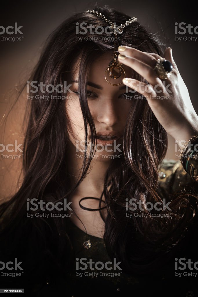 Beautiful woman with fashion make-up and hairstyle like Egyptian princess Cleopatra outdoors against desert stock photo