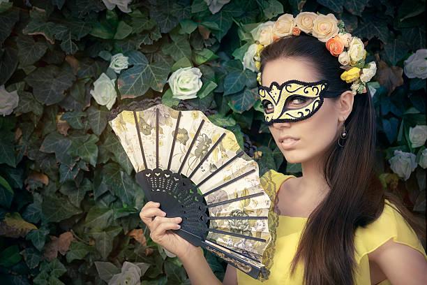 schöne frau mit blumen kranz, maske und fan - geheime garten parties stock-fotos und bilder