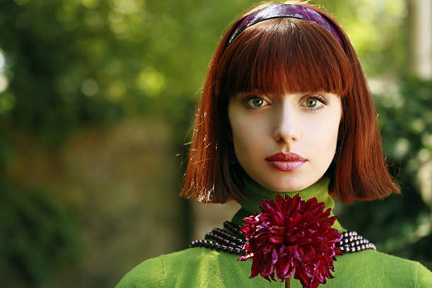 beautiful woman with flower - woman green eyes red hair stock photos and pictures
