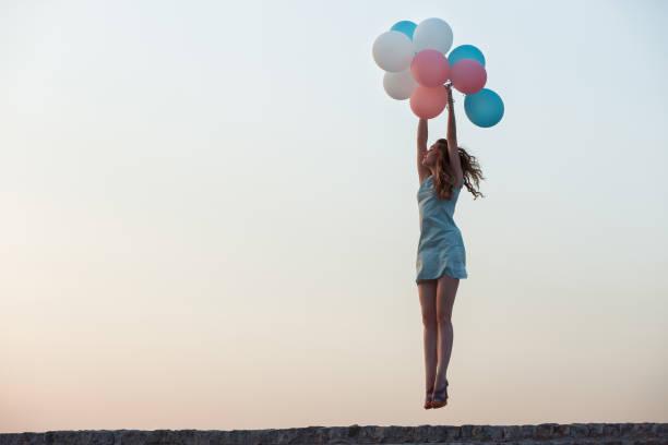 beautiful woman with flying multicolored balloons - mulher balões imagens e fotografias de stock