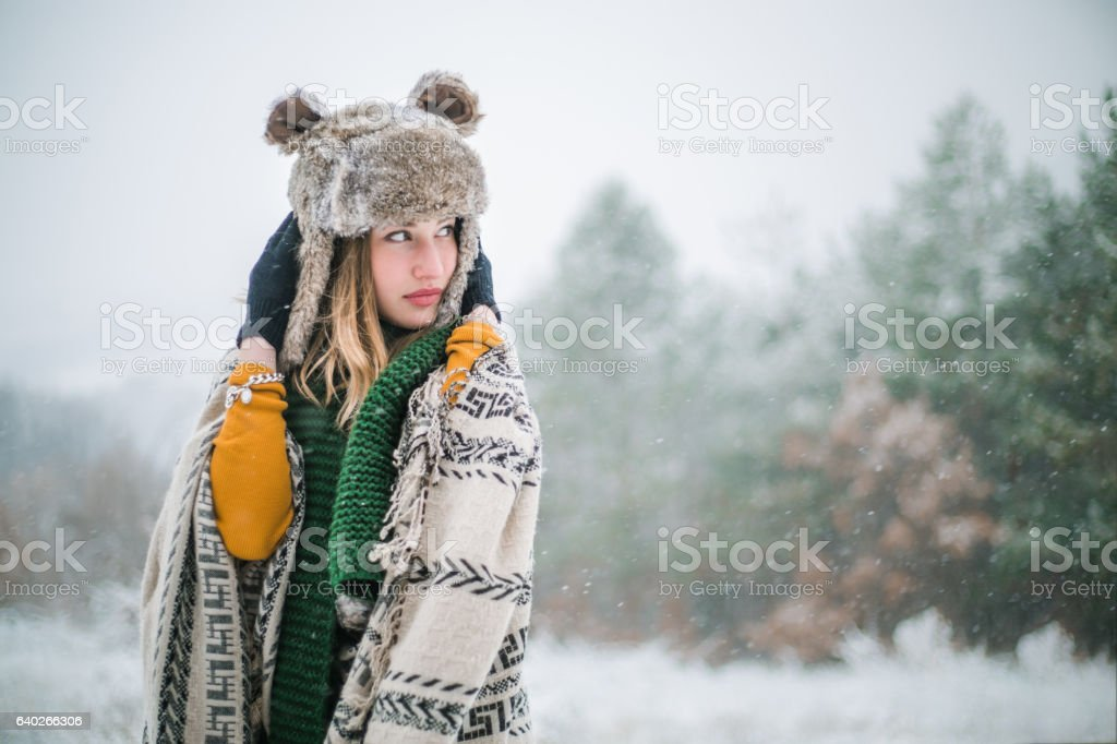 Beautiful woman with fur hat and scarf on snowy day stock photo