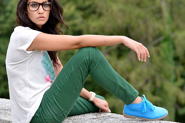 beautiful woman with glasses sitting on wall - flat shoe stock photos and pictures