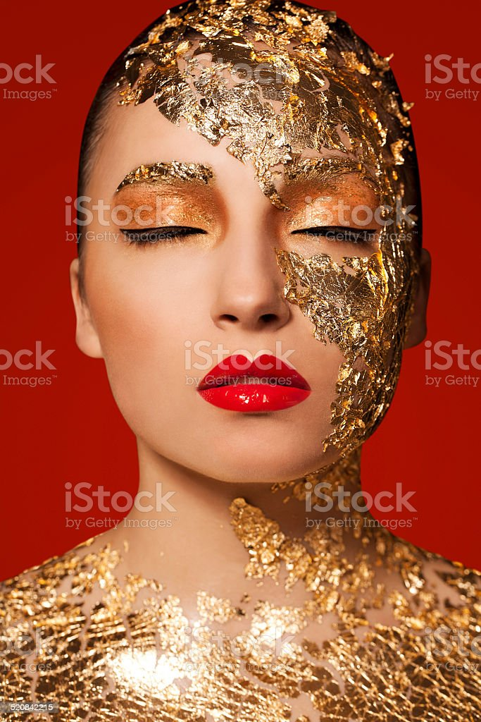 Beautiful woman with gold leaf on her face and body, red lips and...