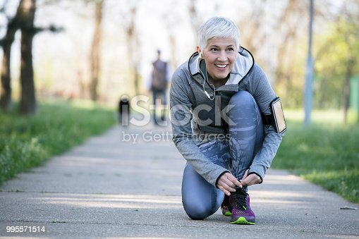 istock Beautiful woman with gray hair in the early sixties relaxing after sport training 995571514