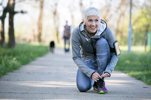 Beautiful woman with gray hair in the early sixties relaxing after sport training In public park at urban environment. Shallow depth of field