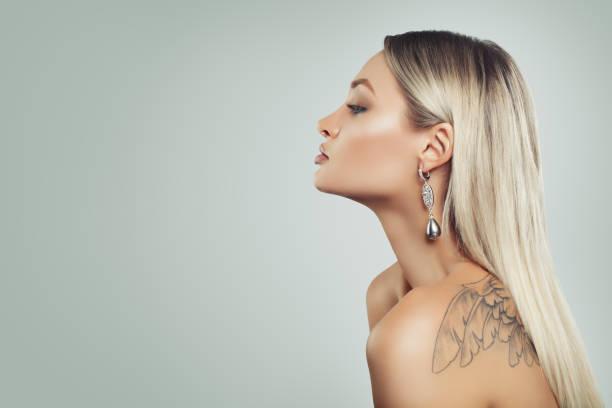 schöne frau mit gesunden blonde haare, make-up und perlen ohrringe auf hintergrund mit textfreiraum - promi schmuck stock-fotos und bilder