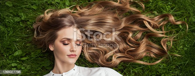 Beautiful woman with healthy curly hair relaxing on green grass outdoor, top view