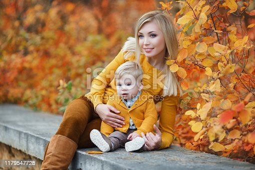 istock Beautiful woman with her young son walk together in an unusually beautiful autumn park 1179547728