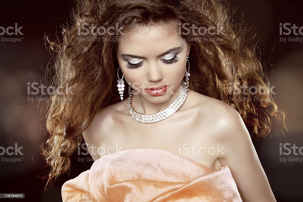Beautiful woman with long brown curly hair and makeup. Hairstyle royalty-free stock photo