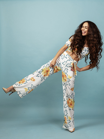 Beautiful woman with long curly hair in floral outfit front of blue background
