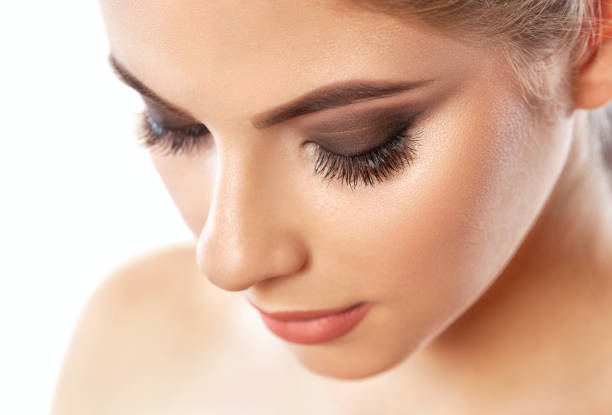 Beautiful woman with long eyelashes, beautiful make-up and thick eyebrows. Beautiful grey eyes close up. Professional makeup and cosmetology skin care. stock photo