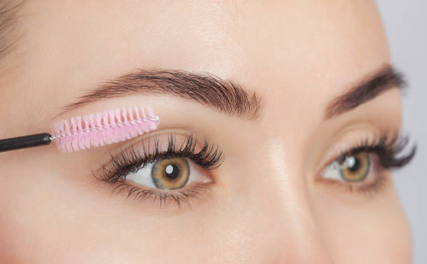 Beautiful Woman with long eyelashes in a beauty salon. Eyelash extension procedure. Cosmetology skin care stock photo