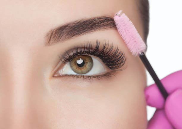 Beautiful Woman with long eyelashes in a beauty salon. Eyelash extension procedure. Lashes close up. Cosmetology concept stock photo
