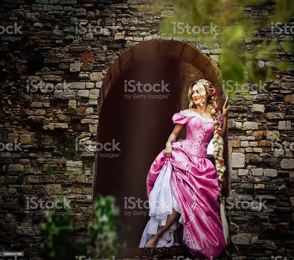 Beautiful woman with long hair in the window of the tower. stock photo