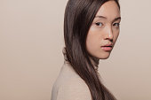 Portrait of woman with straight brown hair. Asian woman with a long hair looking at camera.