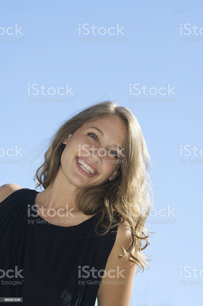 Beautiful Woman with Long Hair Smiling  Against a Blue Sky royalty-free stock photo