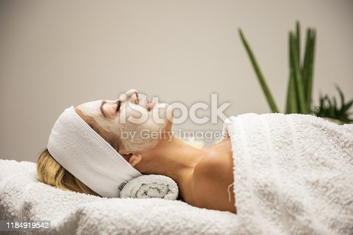Beautiful woman with mask on face in spa beauty salon