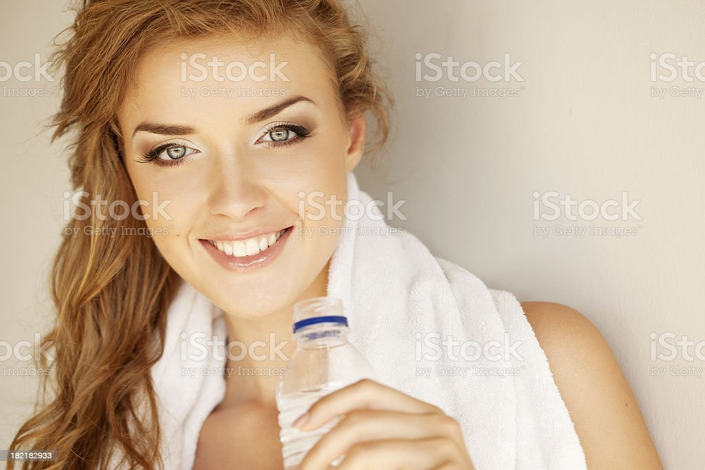 Beautiful woman with mineral water and towel royalty-free stock photo