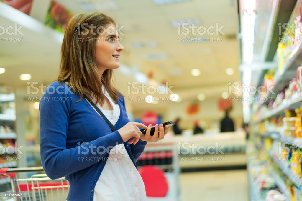 Beautiful woman with mobile phone at supermarket royalty-free stock photo