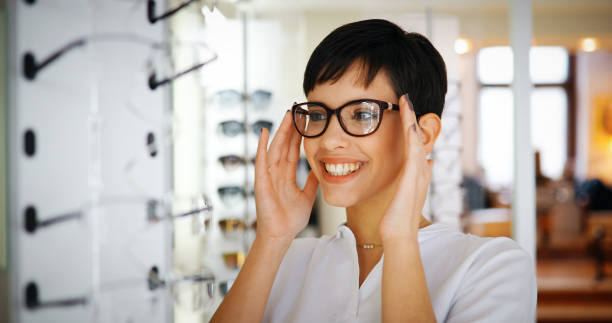 Beautiful woman with optician trying eyeglasses Beautiful woman with optician trying eyeglasses at optics store optical instrument stock pictures, royalty-free photos & images