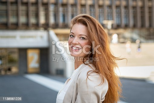 Portrait of beautiful young woman smiling while looking at camera. Mature woman with red hair and freckles looking at camera with big smile. Friendly casaul woman standing on city street feeling happy.