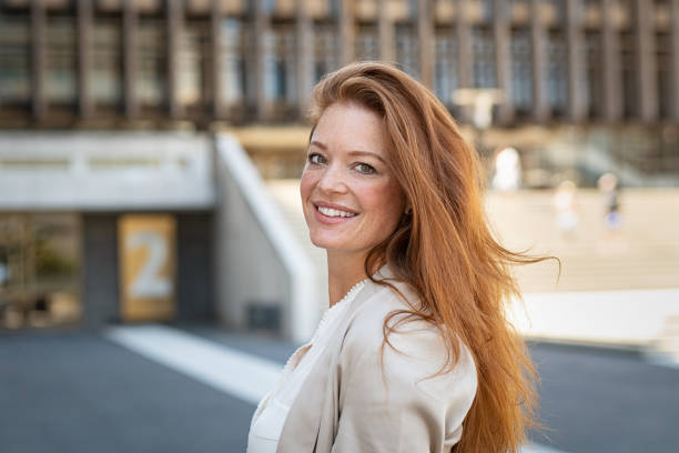 Beautiful woman with red hair Portrait of beautiful young woman smiling while looking at camera. Mature woman with red hair and freckles looking at camera with big smile. Friendly casaul woman standing on city street feeling happy. redhead stock pictures, royalty-free photos & images