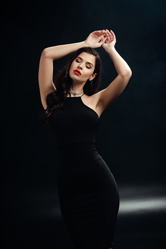 Beautiful woman with red lips and closed eyes on black background