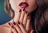 赤い唇とマニキュアの美しい女性