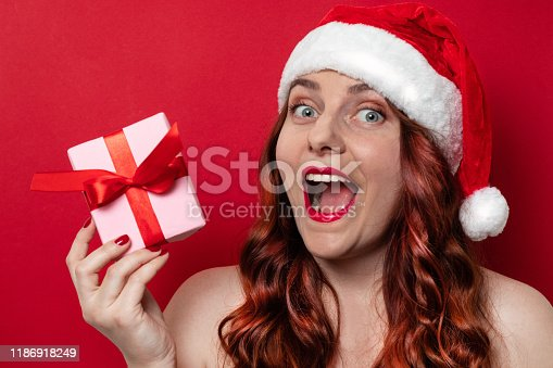 istock Beautiful woman with red santa hat with pompom expressing happy emotions and holding present box on red wall background 1186918249