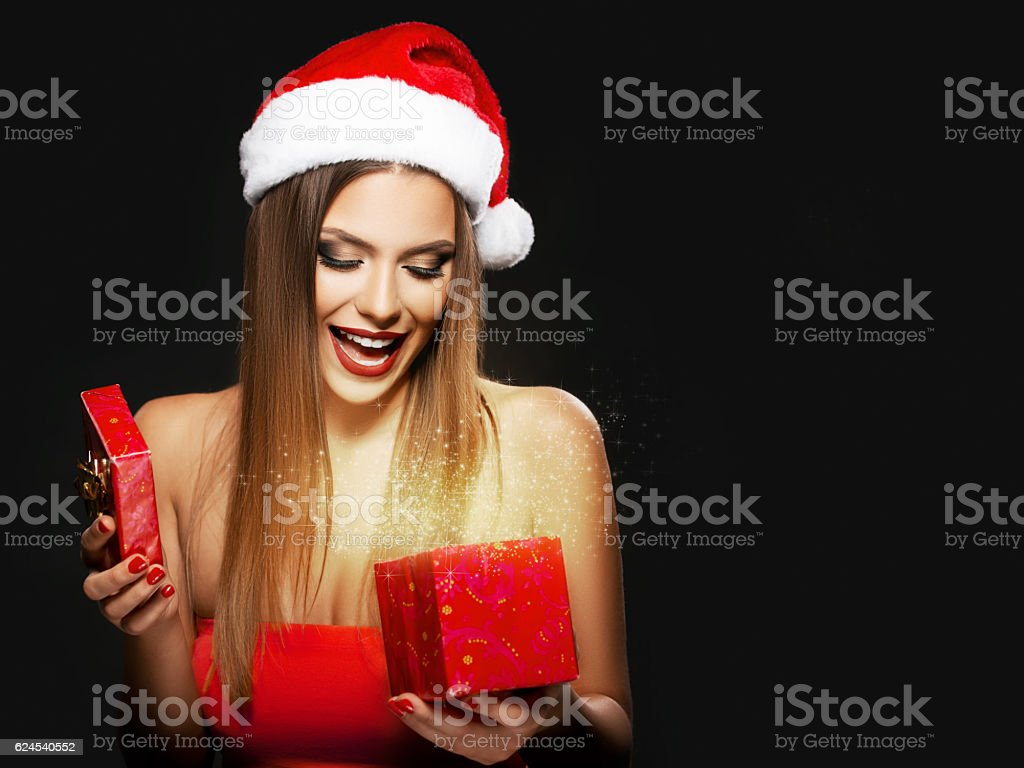 Beautiful woman with Santa's hat opening a present stock photo