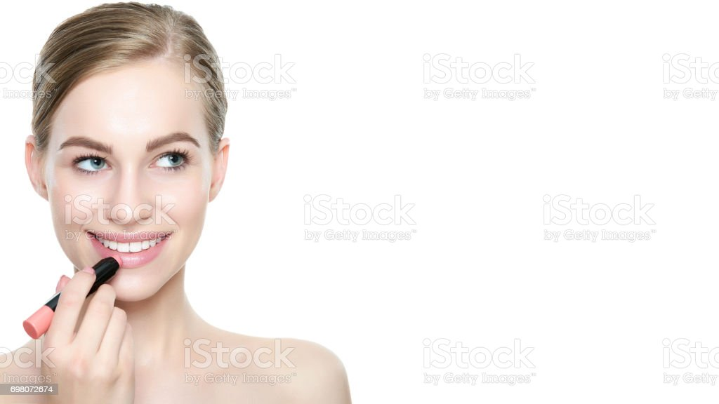 Beautiful woman with sexy full lips applying coral color lipstick. stock photo