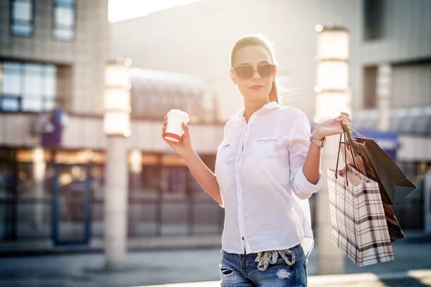 schöne frau mit einkaufstüten und tasse kaffee - besondere geschenke stock-fotos und bilder