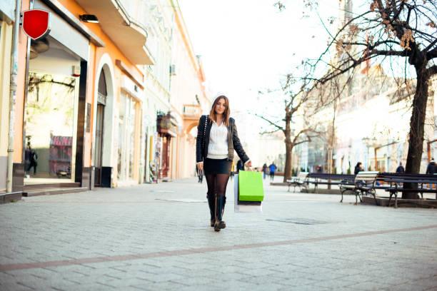 schöne frau mit einkaufstüten - lederjacke mit kapuze damen stock-fotos und bilder