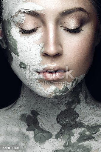 istock Beautiful woman with silver cosmetic mask covering her face 472511696