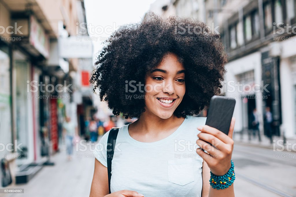 Beautiful woman with smart phone walking on the street stock photo