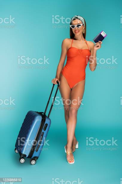 Beautiful woman with suitcase passport and air ticket smiling on blue picture id1220055310?b=1&k=6&m=1220055310&s=612x612&h=pteh9exocetxaor1sqcckltiozn0fkefb5skd4wccrk=